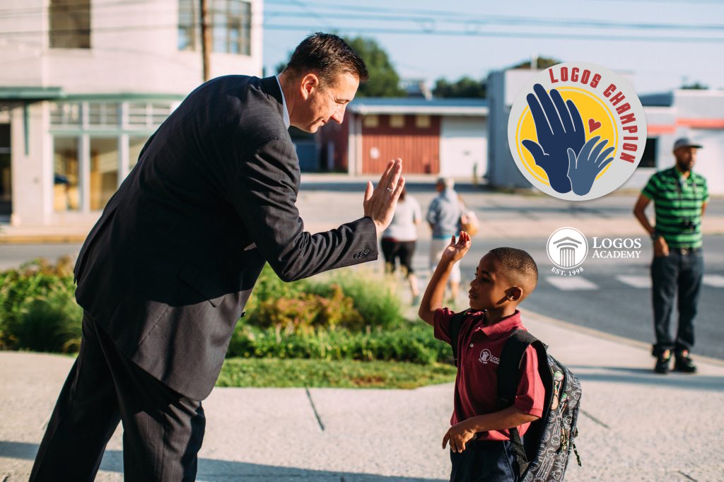 Aaron Anderson, CEO/Head of School, high-fives a student on the first day of school.